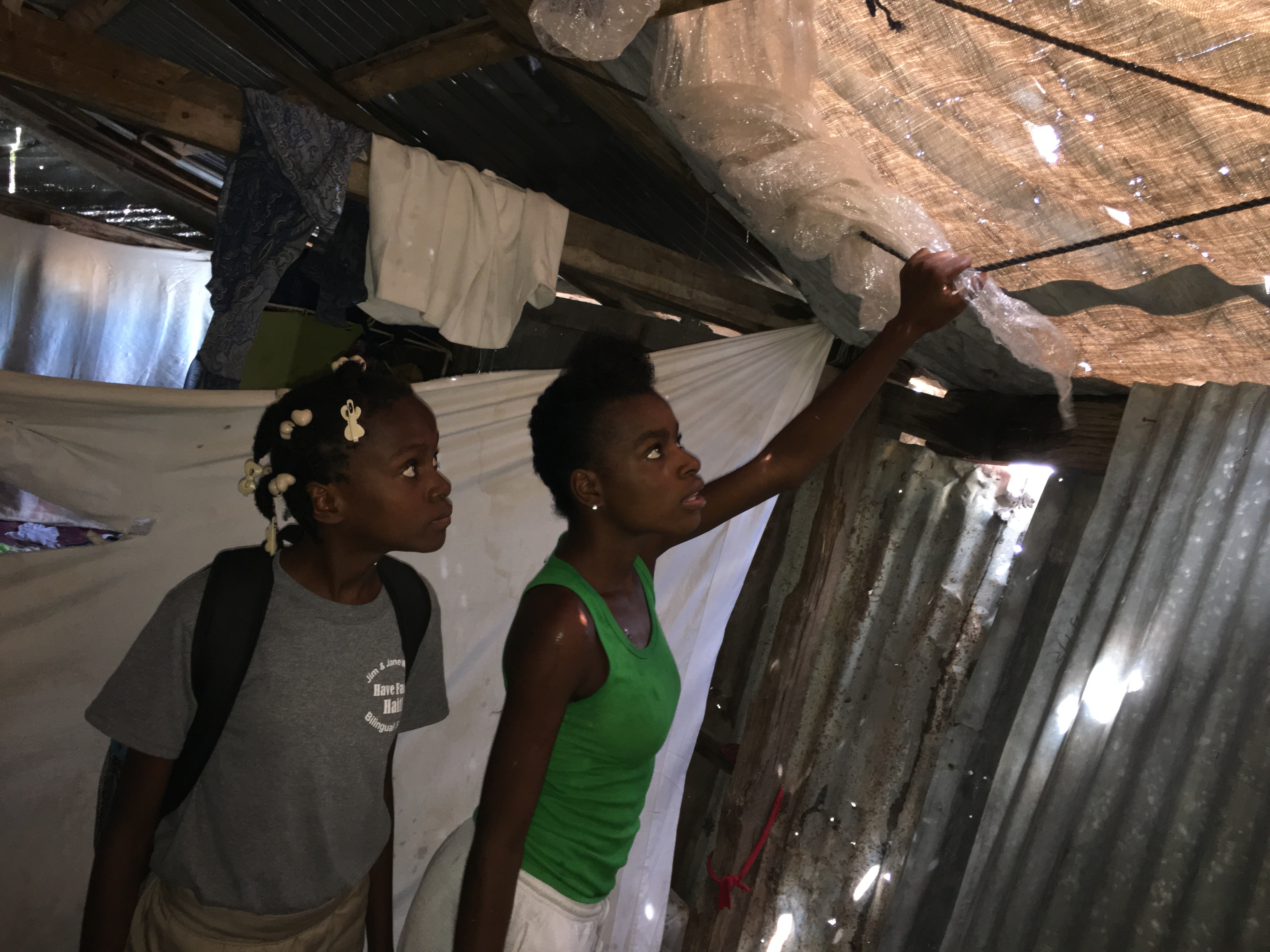 Esterline Nelus, 12 (left) and her sister Stephanie, 16, examine the burlap covering where a tin roof used to be in their tent city village in Port Au Prince. The roof flew away during Hurricane Matthew, flooding their tent and destroying their meager possessions. Esterline is one of 39 children being raised at Have Faith Haiti.